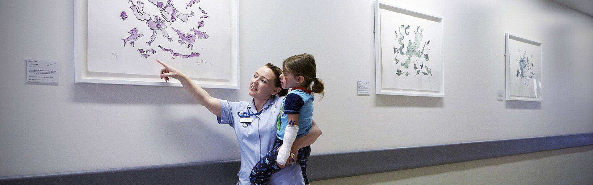 A young patient in the arms of a nurse captivated by Life Under Water 4, 5 and 6 by Quentin Blake. Part of the Paintings in Hospitals collection.
