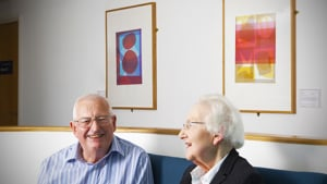 An older man and woman at Bedminster Family Practice, with colourful artworks by Biddy Bunzl on the walls. Part of the Paintings in Hospitals collection.